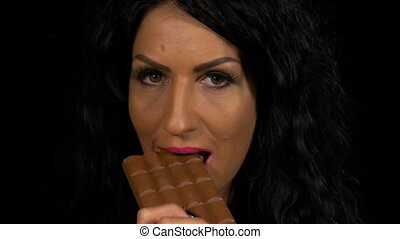 Young woman biting on a piece of dark chocolate closeup