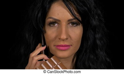 Closeup of attractive female chatting at smartphone while...
