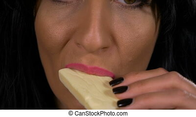 Closeup of sensual female lips tasting white chocolate