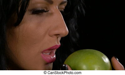 Slow motion of beautiful healthy woman biting and eating a...