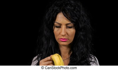 Smiling woman peeling and eating banana