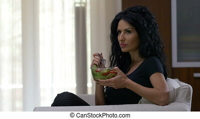 Woman with healthy lifestyle eating a bowl of fresh vegetables salad sitting on couch at home