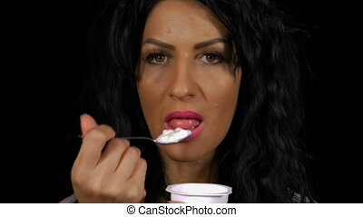 Young healthy woman eating a fresh yogurt low caloric food