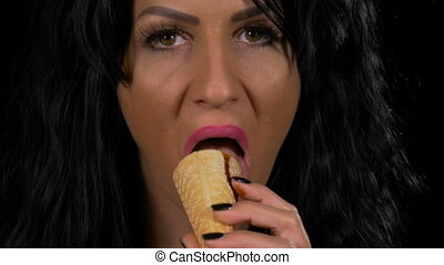 Closeup of seductive woman licking waffle cone from dairy...