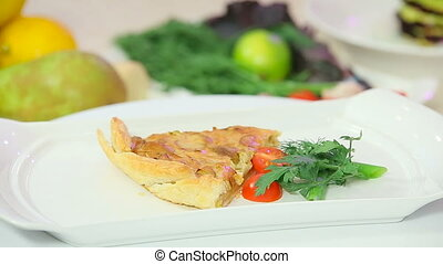 Onion pie garnished with cherry tomatoes presentation