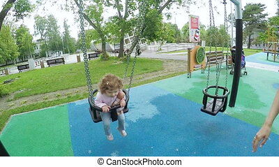 Girl riding on a swing mom - Curly-haired girl riding a...