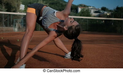 Woman doing exercise for leg buttocks on tennis court.
