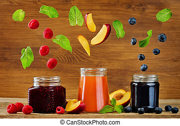 set of jams with flying slices: raspberry, blueberry and peach