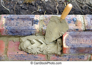 Bricklaying - Bricklayers trowel and mortar on a...