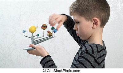 boy turning the models of planets - Little boy studying...