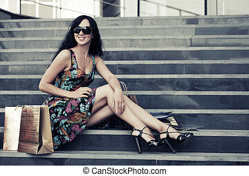 Young fashion woman with shopping bags sitting on the mall...
