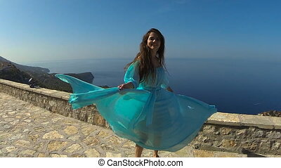 Beautiful happy smiling Girl spinning in blowing blue dress...