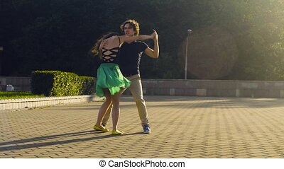 Young couple dancing on the square in the park in summer
