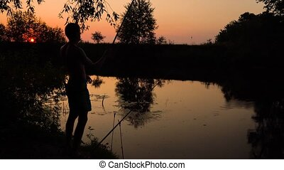 Silhouette of a fisherman on the river bank at sunset