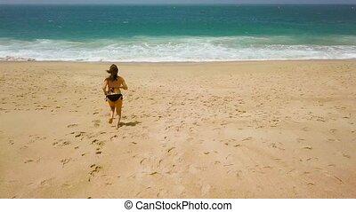 Beach bikini woman carefree running to the water on the...