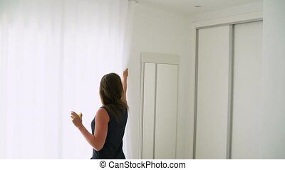 Woman opening her bedroom curtains and drinking orange juice...