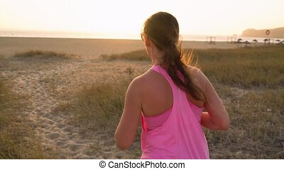 Athletic woman running along the beach to the ocean....