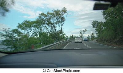 A wide shot of a curvy road with cars.