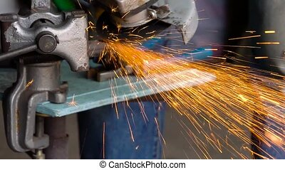 Worker with angular grinding machine is cutting the metal....