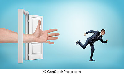 A giant open hand tries to catch a small running businessman through an open white door.