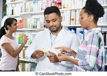 Customer And Chemist With Prescription In Pharmacy
