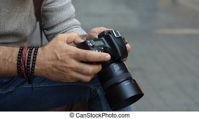 Close up of male hands looking at photo camera
