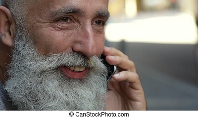 Scaled up look on bearded man talking on phone - Pleasant...