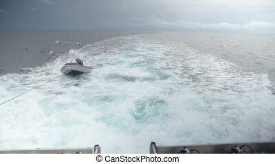Wide shot of the ocean with mini boat