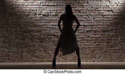 Woman tall in high heels dance twerk against a brick wall....