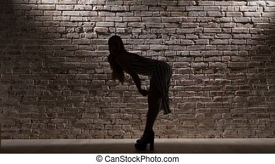 Girl sexy in heels dancing against the light brick wall....