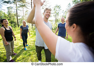Man And Woman Giving High-Five While Friends Standing At...