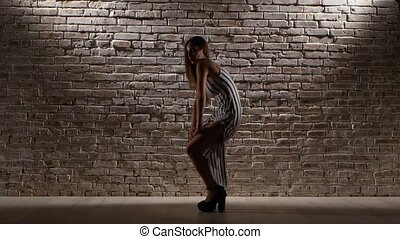 Woman graceful in high heels dance against a brick wall -...