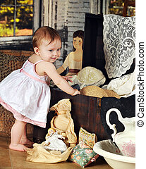 Exploring Grandmas Trunk - An adorable baby girl happily...