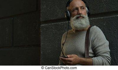 Pensive older man with headphones walking down street -...
