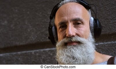 Mature man grinning broadly after taking off headphones -...
