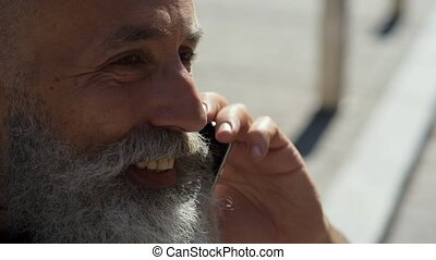 Close up of friendly looking man smiling while talking -...