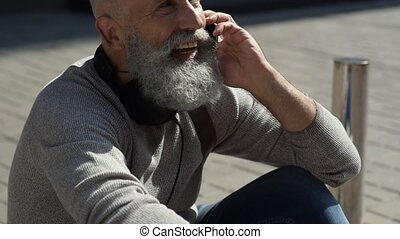 Positive minded bearded guy calling somebody in street - How...