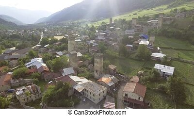Flying over authentic high mountain village in Mestia,...