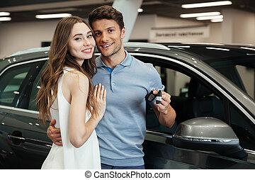 Lady standing near car with boyfriend in car dealership -...