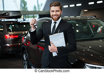 Handsome young car salesman standing at the dealership and...