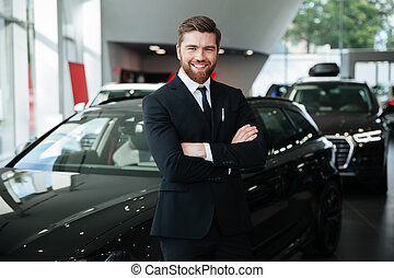 Smiling young male dealer in suit with arms folded standing...