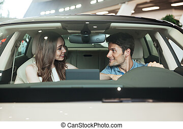 Smiling excited couple sitting inside a new car at the...