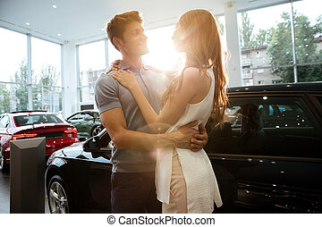 Happy young couple hugging after buying a new car at the...