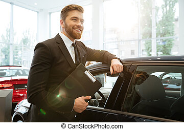 Smiling young car salesman standing at the dealership and...
