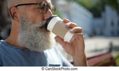 Senior gentleman wearing glasses drinking coffee outdoors -...
