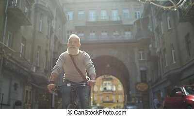 Serious mature guy riding bicycle down street - Time to...