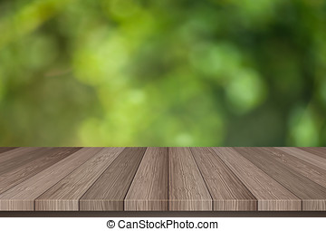 Wooden floor and blurred green trees background.