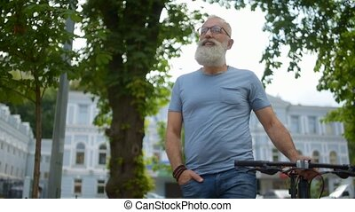 Amazed greyhaired man with bicycle examining city during...
