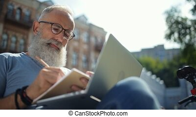 Relaxed mature guy noting down while working outdoors -...