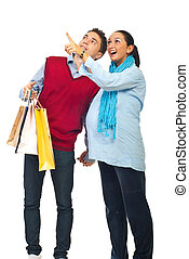 Pregnant couple at shopping pointing up - Happy couple at...